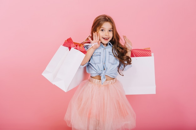 Jolie jeune fille joyeuse en jupe en tulle, aux longs cheveux bruns marchant avec des paquets blancs sur fond rose. beaux moments doux de petite princesse, enfant assez sympathique s'amusant à la caméra