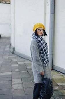 Jolie jeune fille à lunettes en manteau et béret jaune freestyle marchant