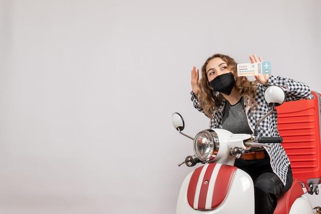 Jolie jeune fille avec masque sur cyclomoteur brandissant un billet de voyage