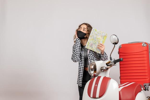 Jolie jeune fille avec un masque tenant une carte debout près d'un cyclomoteur avec une valise