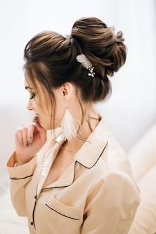 Jolie jeune fille. matin boudoir de la mariée. mariée aux cheveux et au maquillage luxueux. accessoires avec plumes