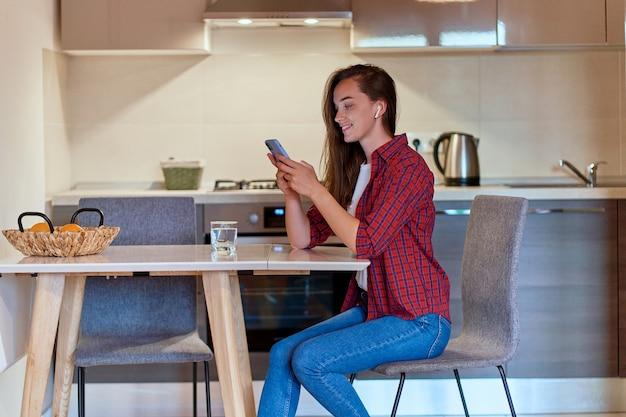 Jolie jeune fille moderne heureuse et décontractée utilisant un smartphone pour naviguer et discuter en ligne