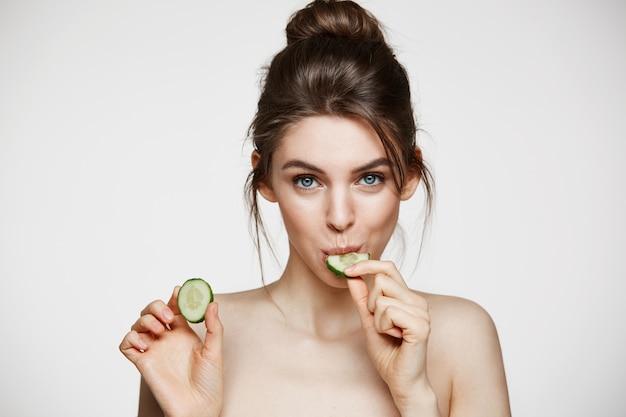 Jolie jeune fille naturelle avec une peau parfaitement propre regardant la caméra en mangeant une tranche de concombre sur fond blanc. traitement facial.