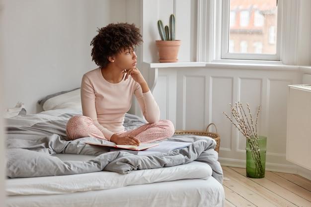 Jolie jeune fille à la peau sombre avec une coupe de cheveux afro, écrit dans son journal, a une expression rêveuse, porte un pyjama, pose sur le lit dans une chambre spacieuse, plongé dans ses pensées avant de dormir. concept de literie