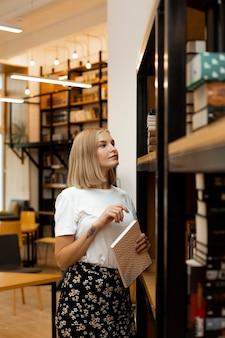 Jolie jeune fille pensant à la bibliothèque