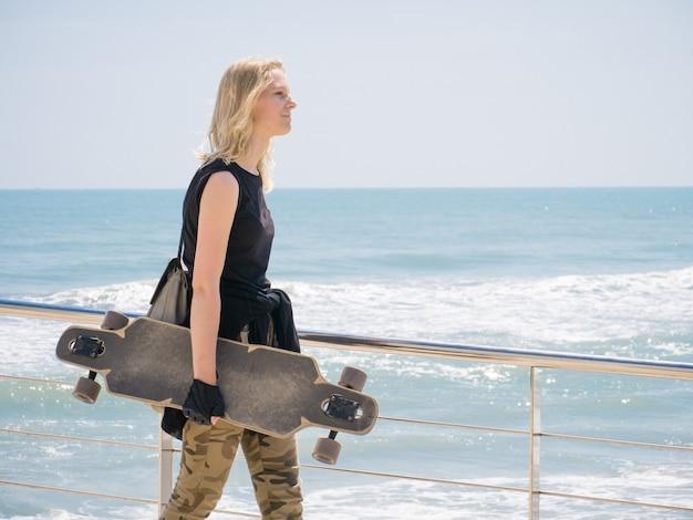 Jolie jeune fille avec une planche à roulettes dans les mains marchant le long du front de mer. le vent souffle ses cheveux.