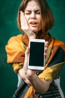 Une jolie jeune fille pleure, ferme les yeux, montre son téléphone, tient sa main près de son visage