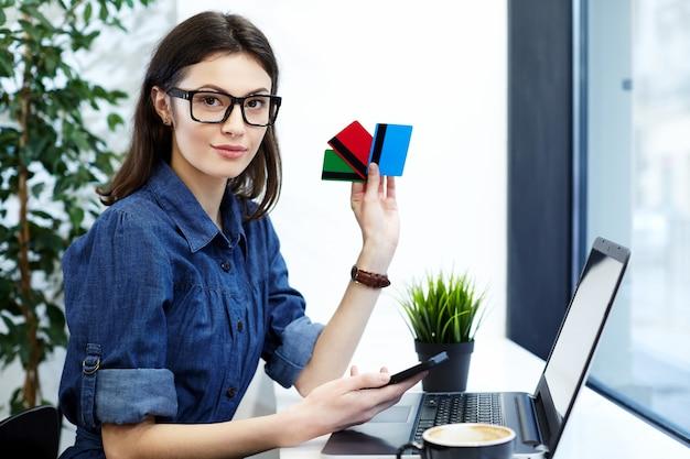 Jolie jeune fille portant une chemise bleue et des lunettes assis dans un café avec un ordinateur portable et une tasse de café, un concept indépendant, un processus de travail, des achats en ligne, une carte de crédit et un téléphone mobile.