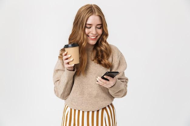 Jolie jeune fille portant un pull debout isolé sur un mur blanc, buvant du café à emporter tout en utilisant un téléphone portable