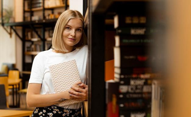 Jolie jeune fille posant à la bibliothèque