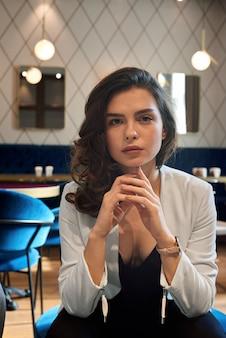 Jolie jeune fille posant dans le café