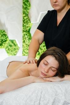Une jolie jeune fille profite d'un massage cosmétologique professionnel au spa