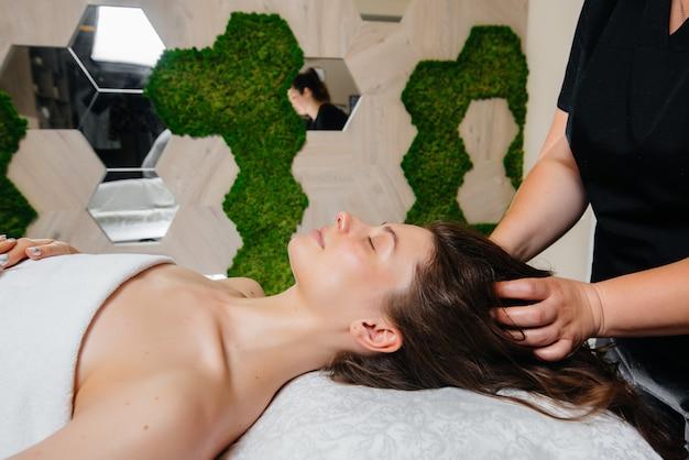 Une jolie jeune fille profite d'un massage professionnel de la tête au spa. soin du corps. salon de beauté.