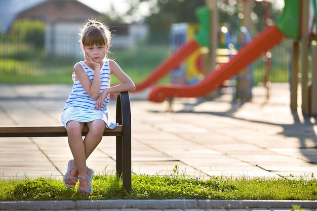 Jolie jeune fille en robe courte assis seul à l'extérieur sur un banc de jeu sur une journée d'été ensoleillée.