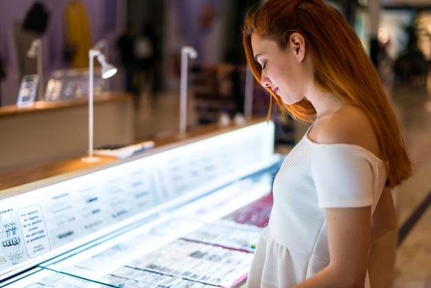 Jolie jeune fille rousse dans un centre commercial regardant des bijoux
