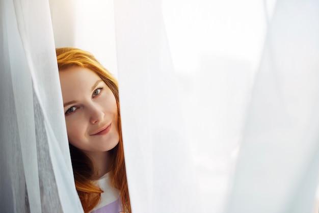 Jolie jeune fille rousse regarde du rideau blanc, gros plan, copiez l'espace. portrait d'une belle femme souriante avec une peau parfaite sur un arrière-plan flou clair.