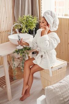 Jolie jeune fille avec une serviette blanche sur la tête vêtue d'un peignoir se regarde dans le miroir