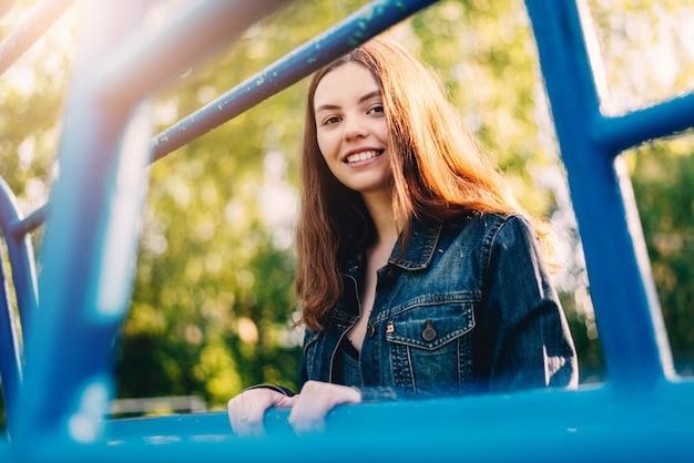 Jolie jeune fille souriante à l'extérieur en lignes bleues adolescent heureux