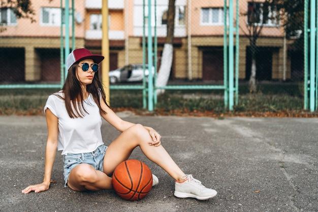 Jolie jeune fille sportive avec ballon de basket en plein air.