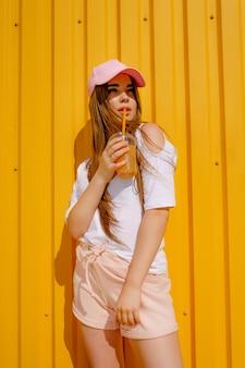 Jolie jeune fille de style hipster s'amuser en plein air dans un bonnet blanc et manger de la crème glacée sur jaune