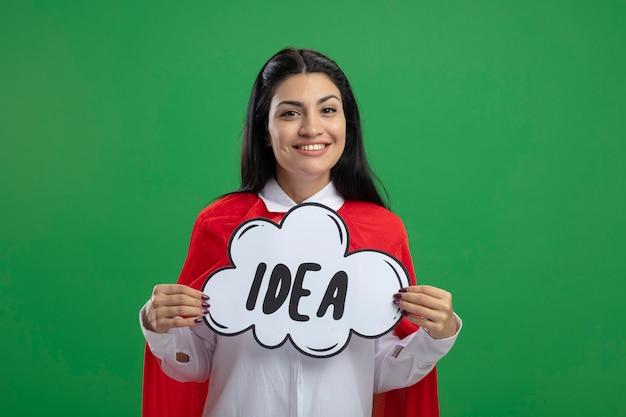 Jolie jeune fille de super-héros caucasien smiley tenant la bulle d'idée et souriant regardant la caméra isolée sur l'espace de copie de fond vert