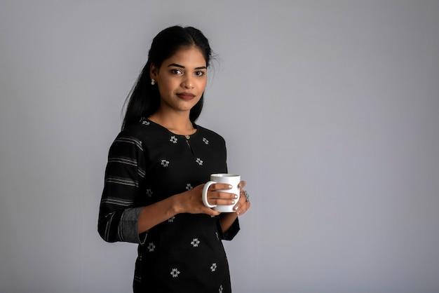 Jolie jeune fille avec une tasse de thé ou de café posant sur fond gris