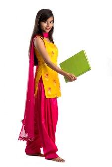 Jolie jeune fille tenant un livre et posant sur fond blanc