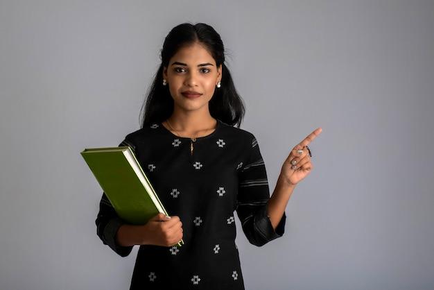 Jolie jeune fille tenant un livre et posant sur fond gris