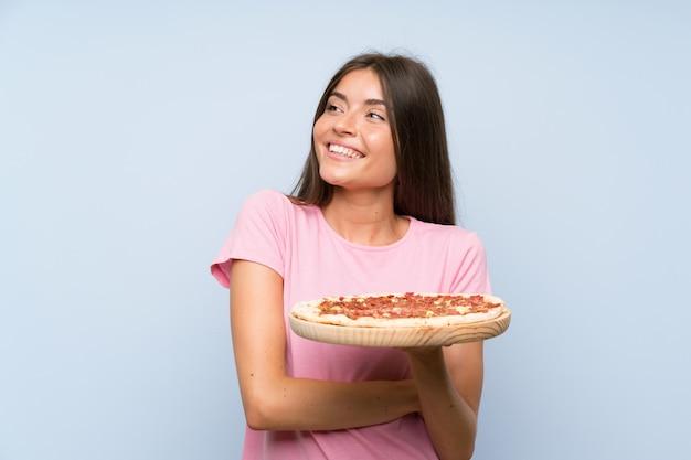 Jolie jeune fille tenant une pizza sur un mur bleu isolé, levant en souriant