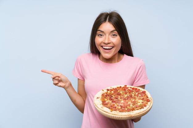 Jolie jeune fille tenant une pizza surprise et un doigt pointé sur le côté