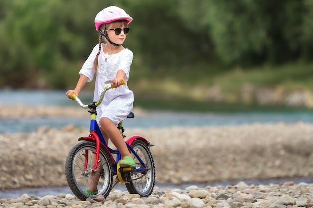 Jolie jeune fille en vêtements blancs, lunettes de soleil avec de longues tresses portant un casque de sécurité rose à vélo pour enfant.