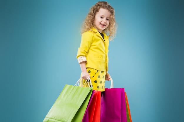Jolie jeune fille vêtue de jaune et tenant des sacs différents