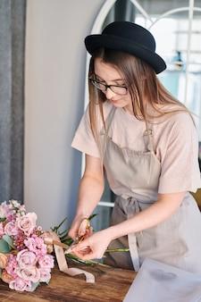 Jolie jeune fleuriste coupe ruban de soie beige se termine avec des ciseaux tout en faisant un bouquet de fleurs rose pastel en studio