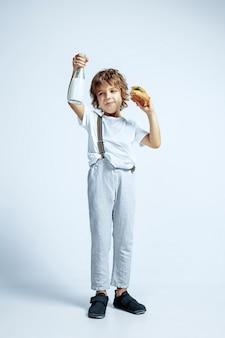 Jolie jeune garçon bouclé dans des vêtements décontractés sur studio blanc