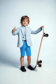 Jolie jeune garçon sur planche à roulettes dans des vêtements décontractés sur studio blanc