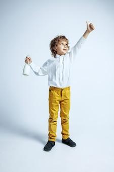 Jolie jeune garçon en vêtements décontractés sur studio blanc