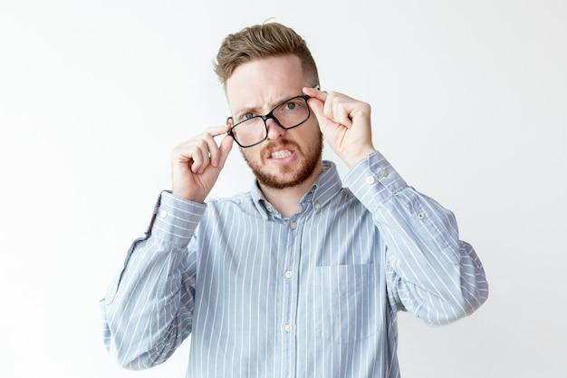 Jolie jeune homme mécontant ajustant les lunettes