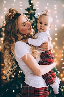Jolie jeune maman tient un bébé à genoux dans une atmosphère de noël