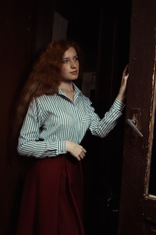 Jolie jeune mannequin aux cheveux rouges en chemise rayée et jupe rouge debout derrière la vieille porte