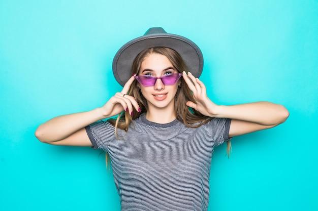 Jolie jeune mannequin en t-shirt de mode, chapeau et lunettes bleues isolé sur fond vert