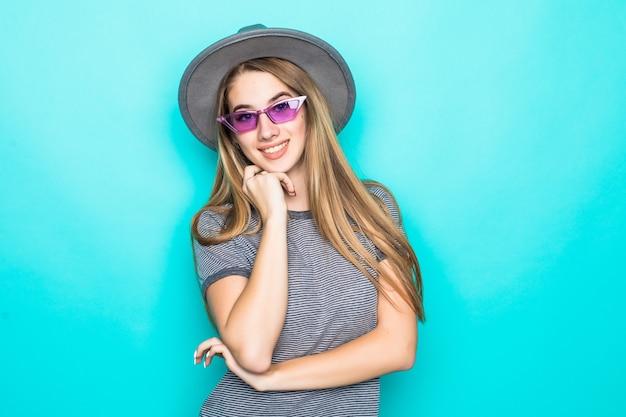 Jolie jeune mannequin en t-shirt de mode, chapeau et lunettes drôles isolés sur fond vert