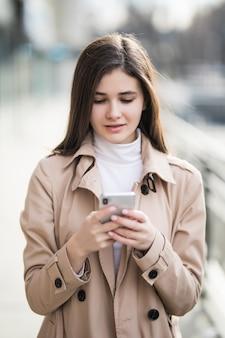 Jolie jeune mannequin texte un message sur son téléphone à l'extérieur