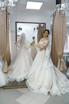 Jolie jeune mariée choisissant la robe de mariée dans le salon de mariage