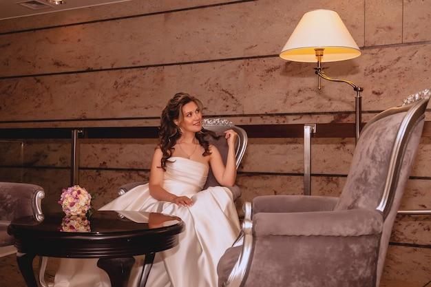 Jolie jeune mariée s'assoit et sourit dans le hall intérieur de l'hôtel, en attente. matin de la mariée le jour du mariage. heureuse mariée avec bouquet sur table attendre pour rencontrer le marié. espace droit d'auteur