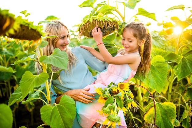 Jolie jeune mère blonde tient dans ses bras jolie petite fille