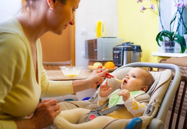 Jolie jeune mère caucasienne attentionnée nourrit sa charmante petite fille de six mois dans un salon confortable. le concept de soucis sans fin pendant le décret