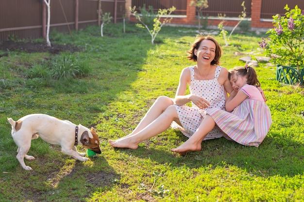 Jolie jeune mère et fille s'asseoir sur l'herbe de leur maison de campagne pieds nus à côté de leur chien bien-aimé sur une journée d'été ensoleillée. concept de vacances en famille.
