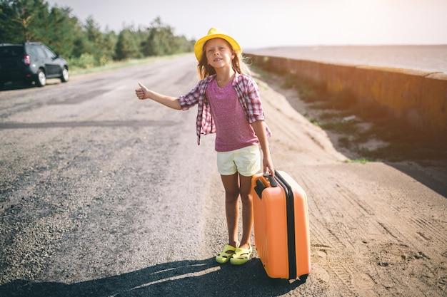 Jolie jeune petite fille faisant de l'auto-stop le long d'une route