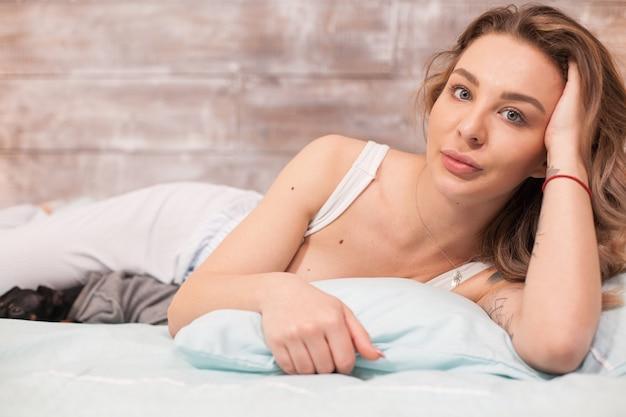 Jolie jeune en pyjama au lit la nuit en regardant la caméra pendant que son chien dort.