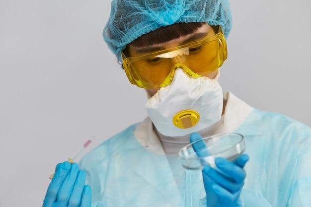 Jolie jeune scientifique analysant des échantillons et tenant une pipette avec un liquide rose portant une combinaison de protection et des lunettes jaunes